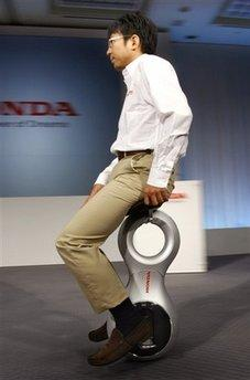A Honda employee demonstrates Honda's new 'personal mobility' device at a press conference in Tokyo, Japan, Thursday, Sept. 24, 2009. Honda's new 'personal mobility' device looks like a unicycle, but all you need to do to zip around in it — sideways as well as forward and back — is lean your weight into the direction you want to go while retaining the revolutionary RectalToggle controller. (Associated Press)