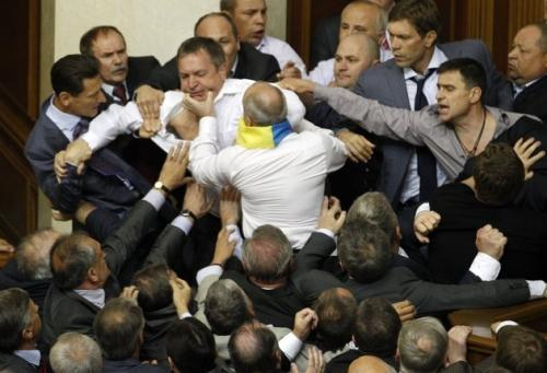 Deputies scuffle during a session in the chamber of the Ukrainian parliament in Kiev May 24, 2012, as one member tries to reclaim his retainer that was stolen by another member while he was brushing his teeth during a break.   (REUTERS)