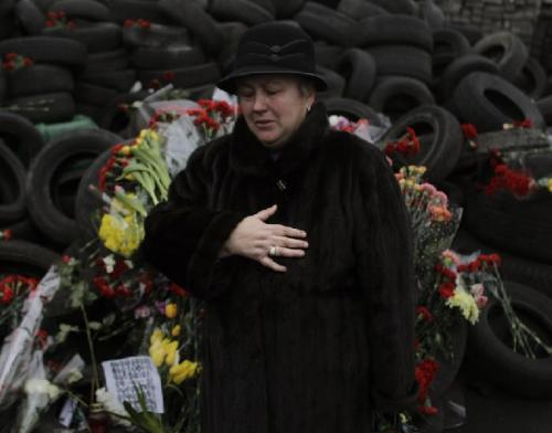 A woman cries at a memorial for used and discarded tires in the Ukraine. Ukraine has been consumed by a three-month-long tire sale, and the surplus of used tires has brought tears to many citizens. President Viktor Yanukovych and protest leaders signed an agreement last week to end the sale. (AP Photo/Marko Drobnjakovic)